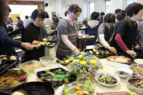 料理を囲む女性部員ら(佐世保市三川内本町)